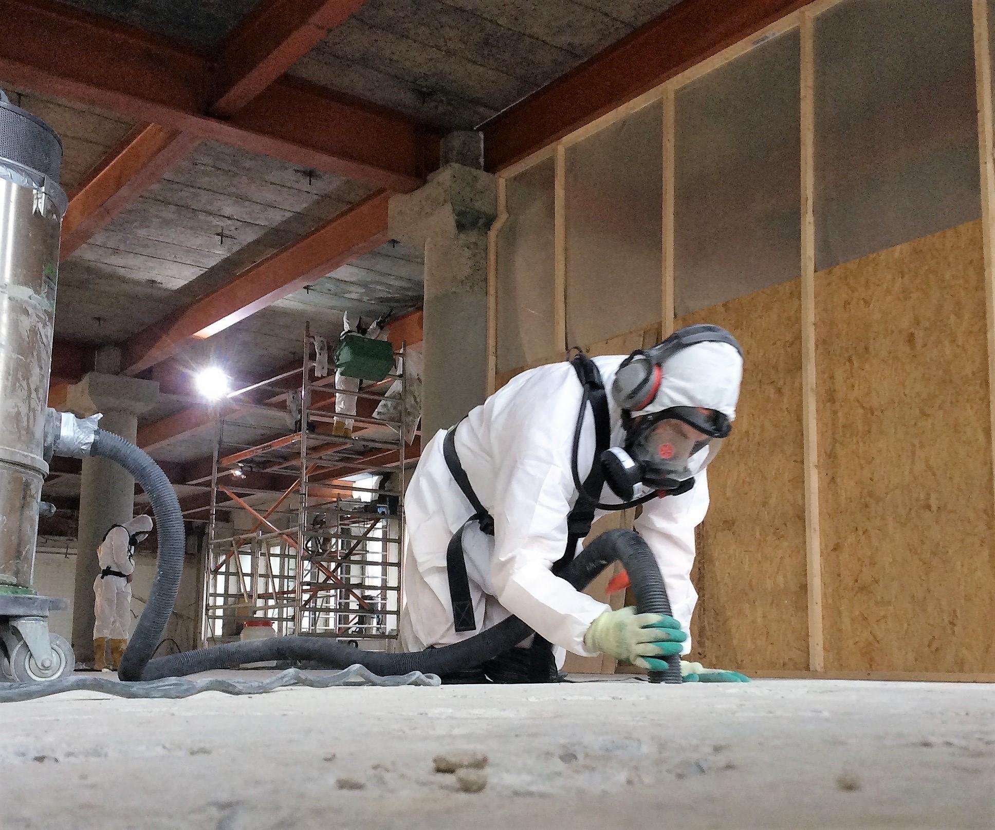 Medewerker Asbestverwijdering Flory BV stofzuigt na Asbestsanering van spuitasbest